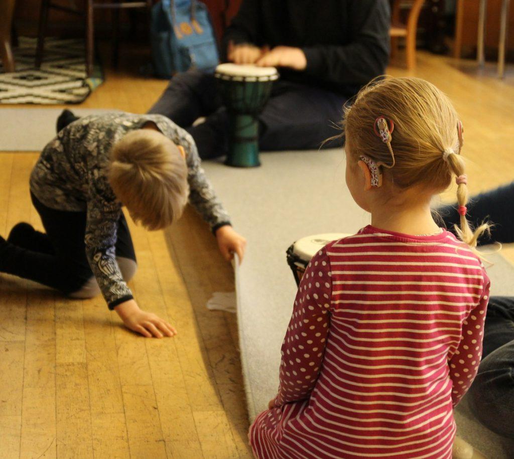 Kuvassa kaksi SI:ta käyttävää lasta leikkii, takana näkyy aikuinen soittamassa bongorumpua