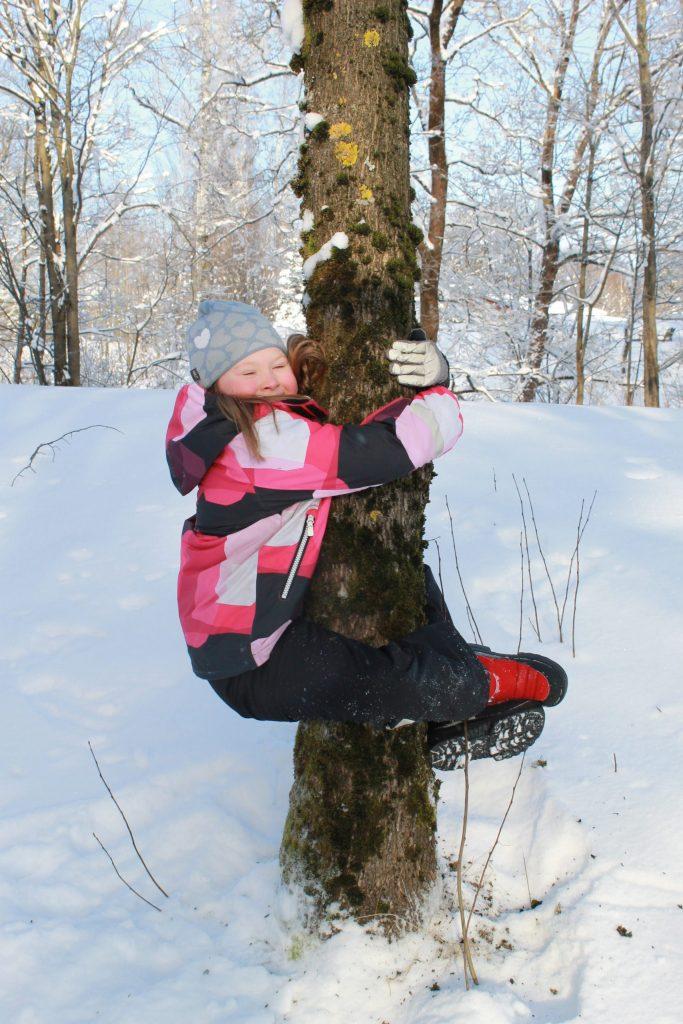 Iloinen lapsi kiipeämässä puuhun talvimaisemassa.