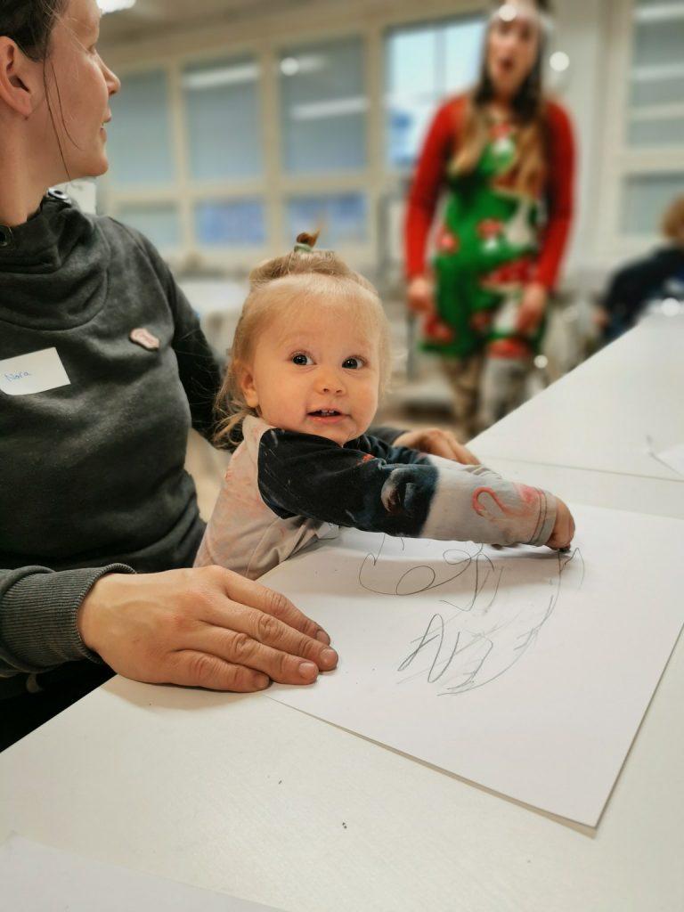 Kuvassa pieni taapero äitinsä sylissä piirtää edessä olevalle paperille. Takana näkyy ohjaaja visiiri päässä.  / Ensitieto-kyselyn tuloksia