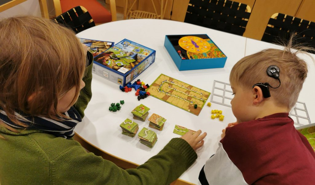 Kuvassa kaksi sisäkorvaistutetta käyttävää lasta pelaa pöydän ääressä lautapeliä