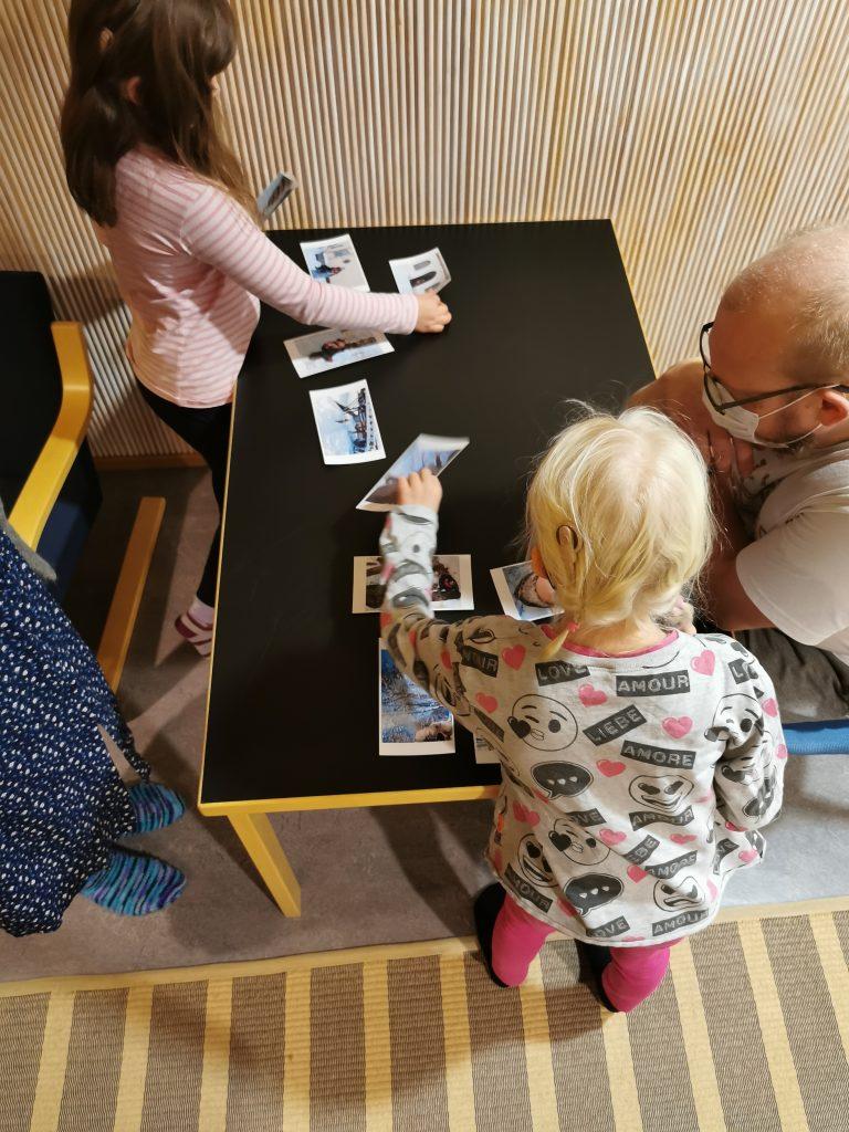 Ylhäältä päin otettu kuva: kaksi lasta valikoi pöydän ääressä kuvia, kaksi aikuista seuraa sivuilla.