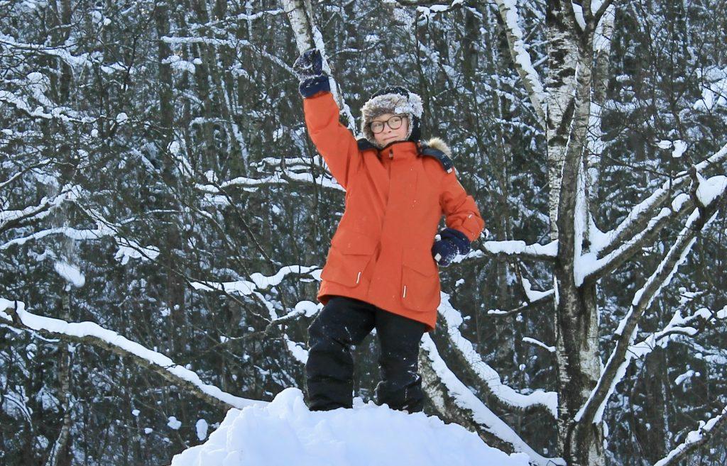 Lapsi poseeraa lumisen metsän edessä punaisessa takissaan Voimauttava valokuvaus -viikonloppuna