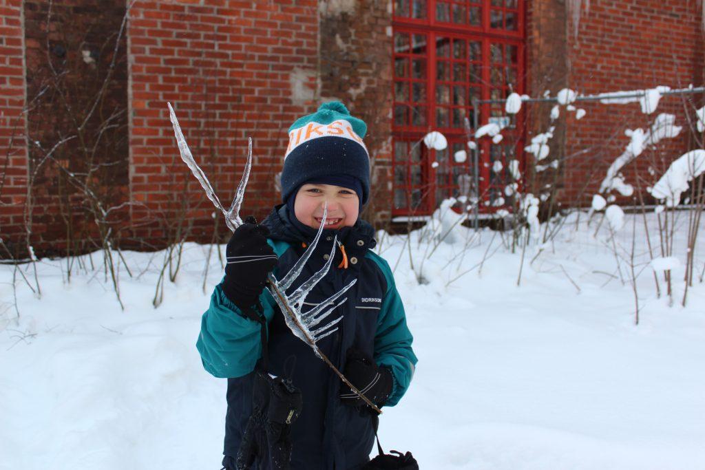 Lapsi poseeraa jääpuikoksi jäätyneen risun kanssa irvistäen Voimauttava valokuvaus -viikonloppuna