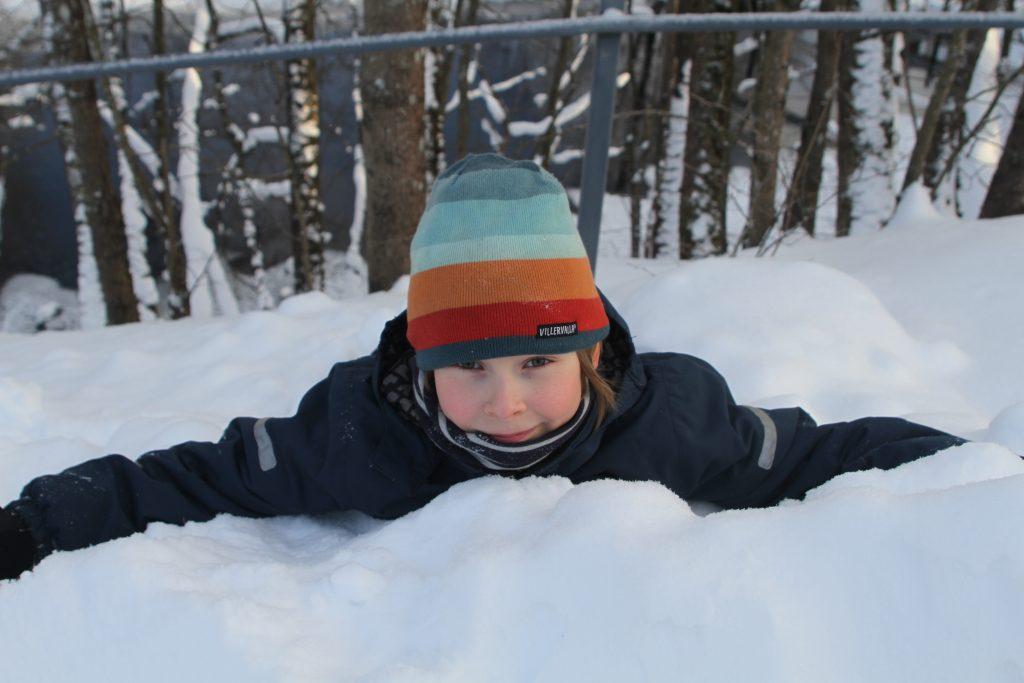 Lapsi makaa mahallaan lumessa ja katsoo kameraan, taustalla puita ja joki Voimauttava valokuvaus -viikonloppuna