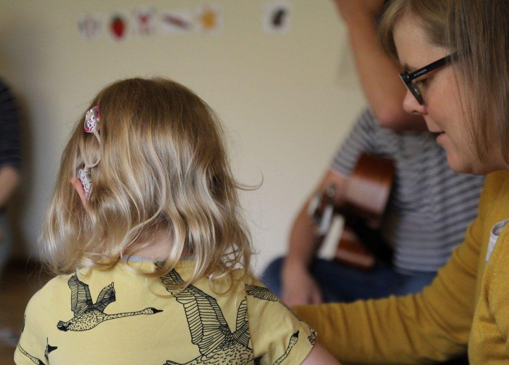 Kuvassa pieni lapsi takaapäin kuvattuna, lapsella sisäkorvaistute. Vieressä aikuinen