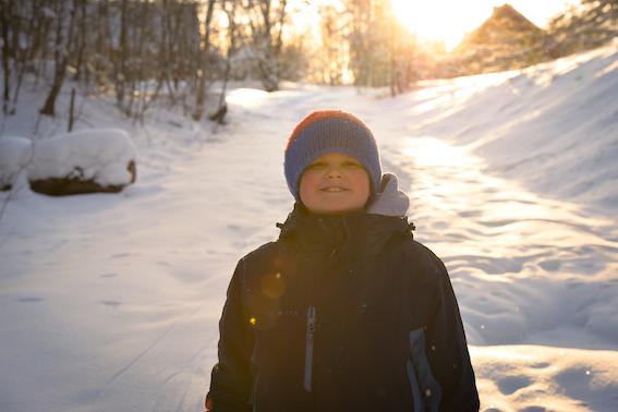 Lapsi poseeraa vastavaloon Voimauttava valokuvaus -viikonlopun talvimaisemassa.