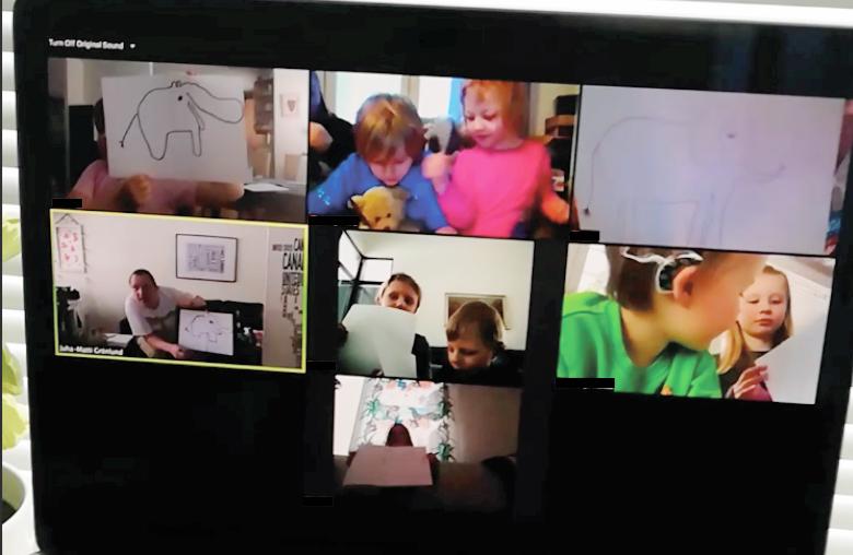 Kuvassa tietokoneruudulla lapset esittelevät piirroksiaan.
