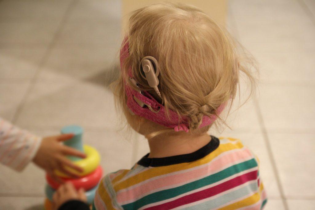 Kuvassa pieni lapsi kuvattuna takaapäin, hänen päässään sisäkorvaistute
