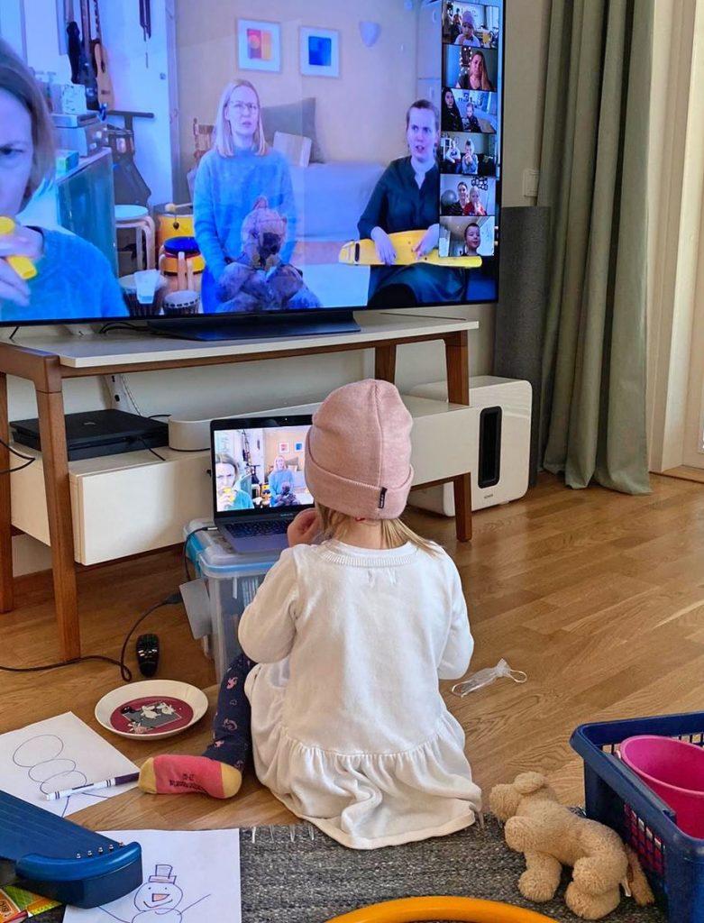Kuvassa pieni lapsi istuu läppärin ja TV:n edessä, molemmissa ruuduissa näkyy CIsumusan ohjaajia