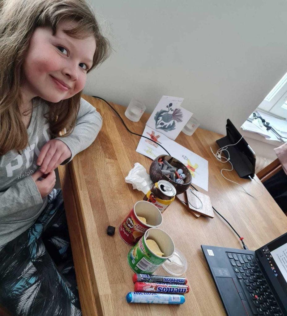 Kuvassa tyttö poseeraa pöydän vieressä, pöydällä erilaisia sipsejä, karkkia ja limua.  / Vuosikokous