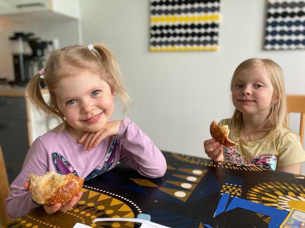 Kuvassa kaksi lasta syömässä pullaa pöydän ääressä