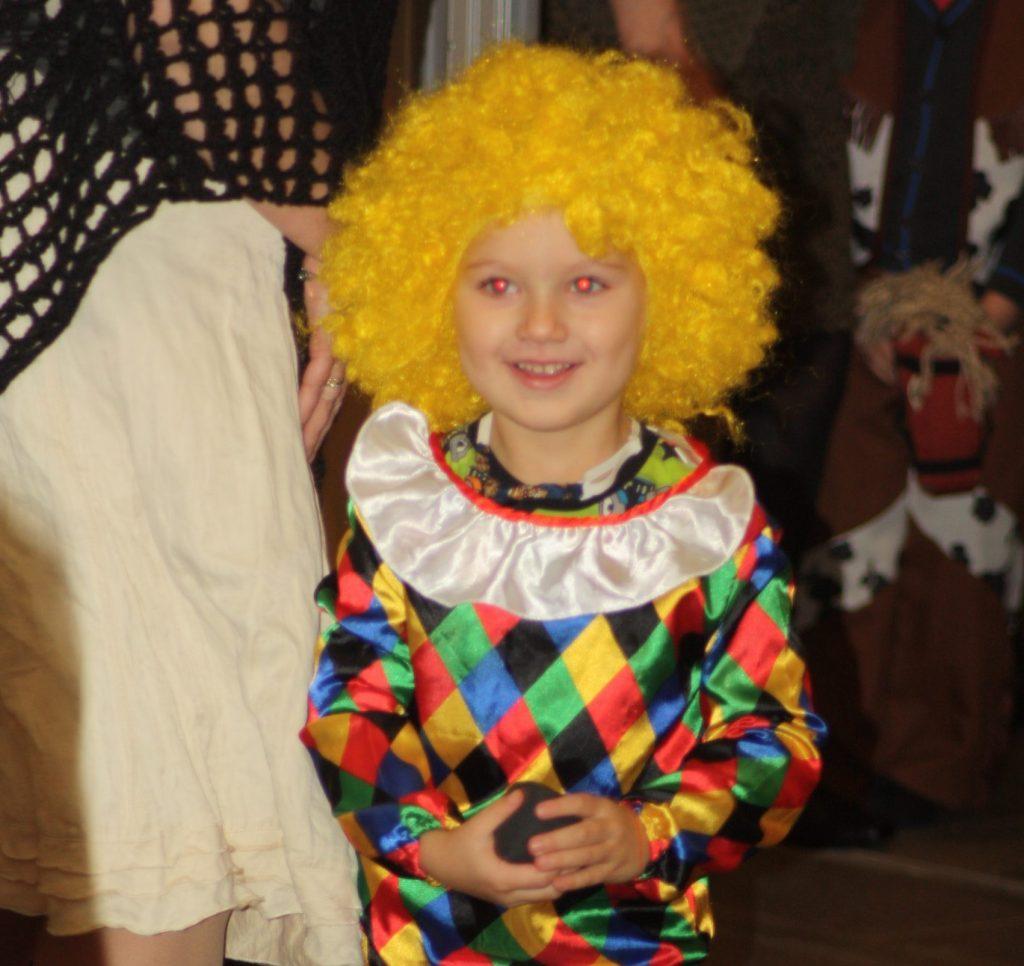Kuvassa lapsi pukeutuneena keltaiseen peruukkiin ja värikkääseen harlekiiniasuun.  / Ensitieto ja kuulon kuntoutus