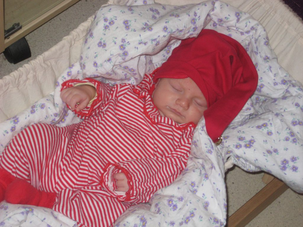 Kuvassa vauva nukkuu tonttulakki päässään ja puna-valkoraidallinen haalari päällään.  / Ensitieto ja kuulon kuntoutus