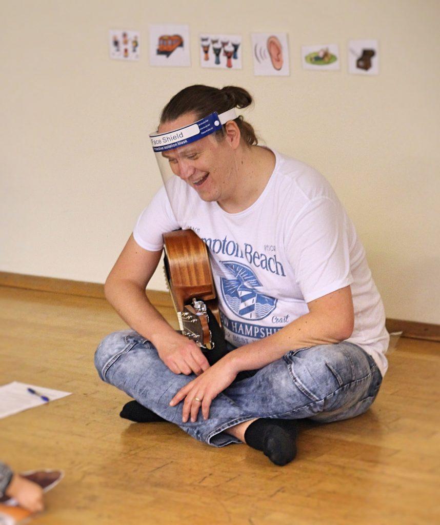 Kuvassa Kuulomuskari ohjaaja Juha-Matti istuu lattialla kitara sylissä.