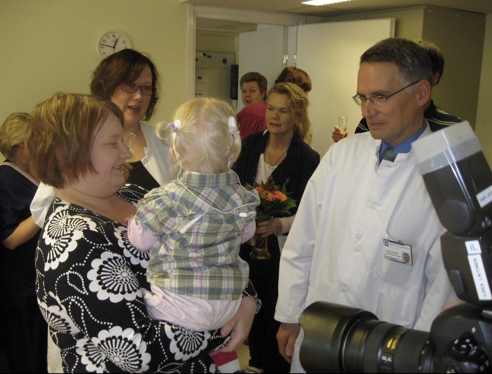 Kuvassa Minna Mäkelä SI:ta käyttävä lapsi sylissään, ympärillä ihmisiä ja vieressä lääkäri.