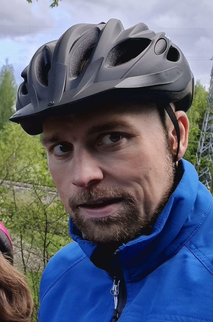 Kuvassa etualalla Lasse Vilminko päässään pyöräilykypärä.