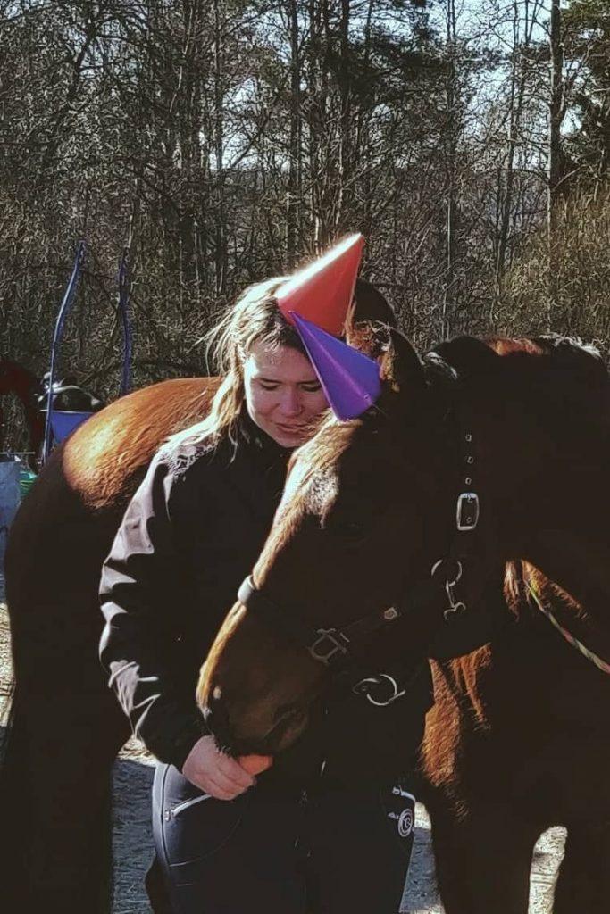 Kuvassa Katariina vierellään Holly hevonen. Molemmilla päässään paperihatut Hollyn synttäreiden kunniaksi.
