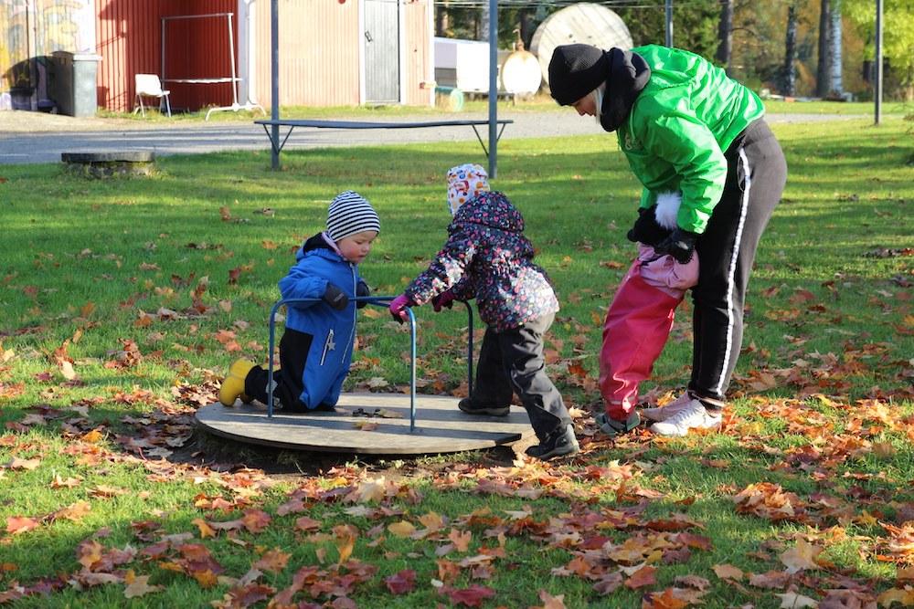 Kuvassa nuori ohjaaja on kolmen pienen lapsen kanssa pienen karusellin ääressä leikkimässä.