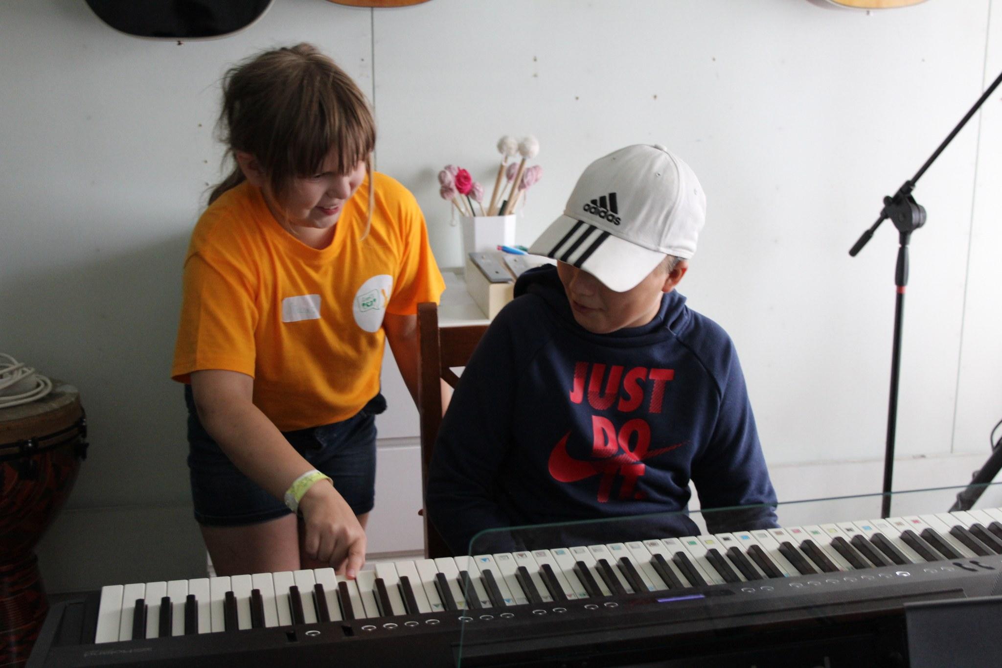 Kuvassa tyttö ja poika pianon äärellä, tyttö painaa painon kosketinta