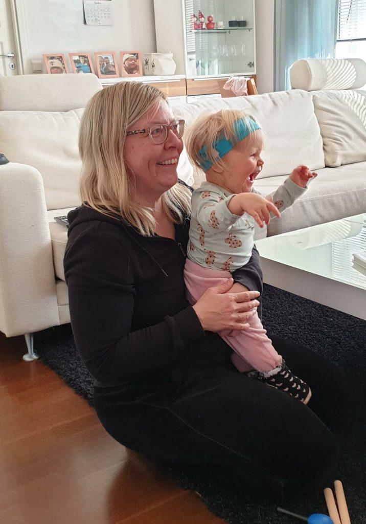 Kuvassa äiti ja lapsi sylikkäin hymyillen istuvat lattialla, lapsi heiluttaa käsiään.