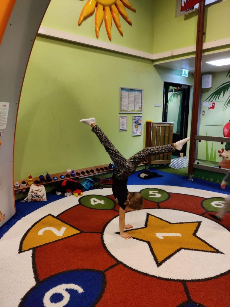 Kuvassa leikkihuone, missä lapsi seisoo käsillään