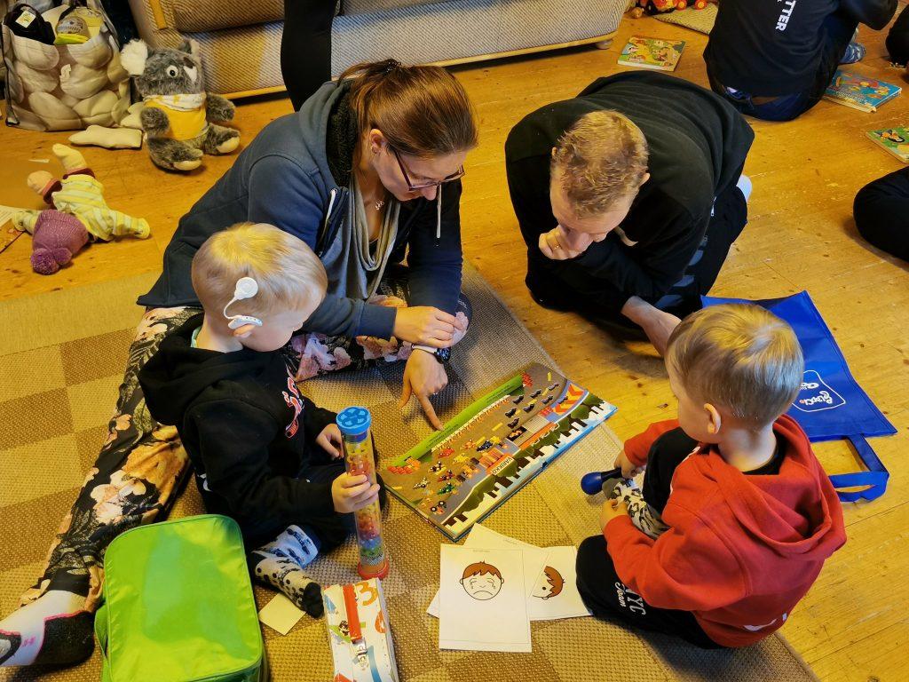 Kuvassa nelihenkinen perhe ringissä kuvakirjan ympärillä. Toisella lapsista on sisäkorvaistute. Ympärillä lattialla leluja, kasseja ja kirjoja.