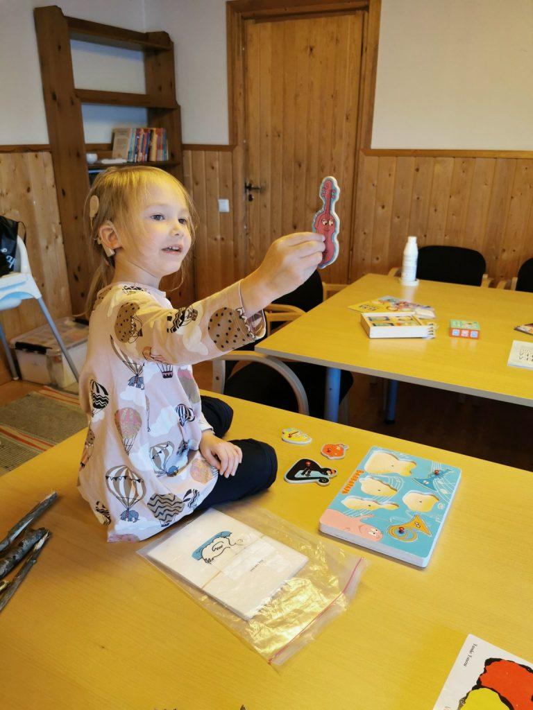Kuvassa pieni sisäkorvaistutta käyttävä tyttö istuu pöydän päällä ja pitää kädessään palapelin palikkaa. Pöydällä ja vieressää näkyy erilaisia kirjoja ja palapelejä