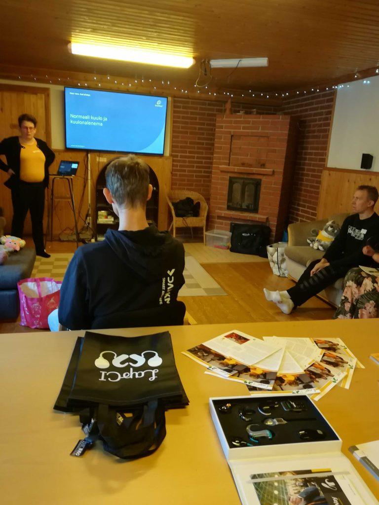 Kuvassa Ulla Konkarikoski seisoo taka-alalla powerpoint-esityksen vieressä. Etualalla näkyy vanhempia istumassa ja kuuntelemassa.