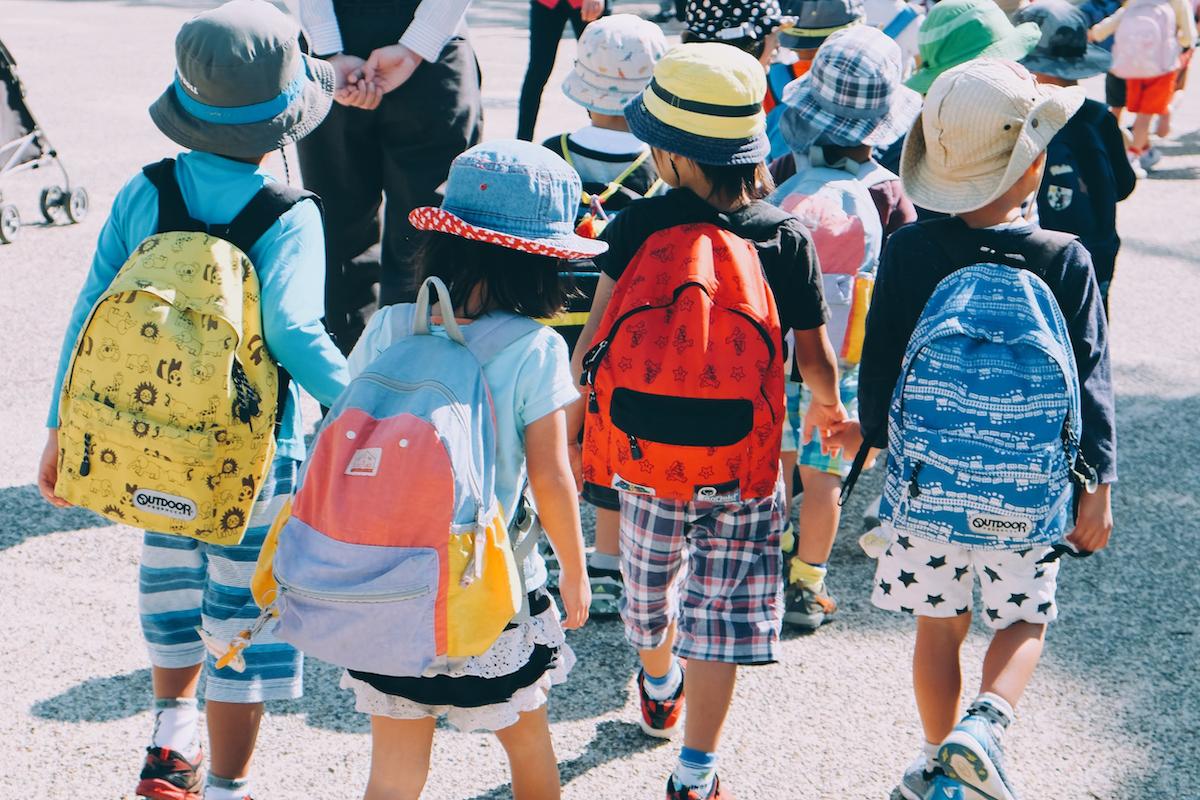 Kuvassa lapsia kuvattuna takaapäin, lapsilla selässä koulureput.